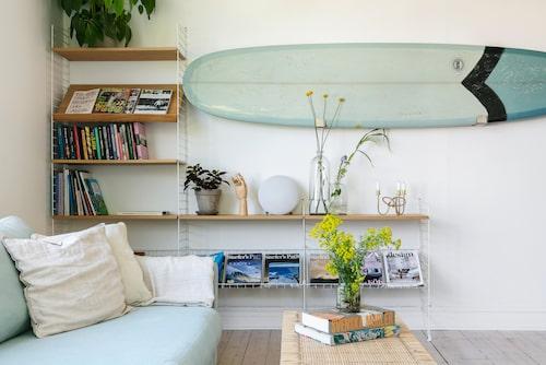 Moas stora intresse är inredning: Nils är surfing. Vardagsrummets Stringhylla rymmer tidningar och böcker på temat, men också några vackra inredningsdetaljer som Svenskt Tenns ljusstake Vänskapsknuten i mässing. Soffa från Sweef och soffbord från Ikea.