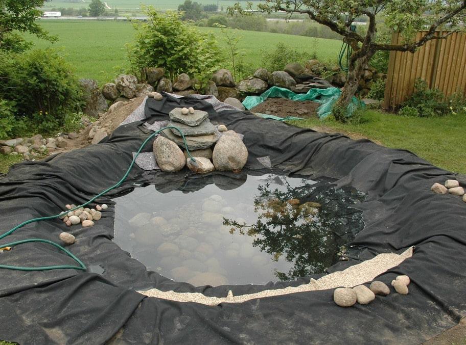 9. SKRUBBA STENARNA Medan vattnet sakta fylldes på placerades några av de finaste stenarna på botten och runt kanterna. Först hade de skurats och gjort rena.