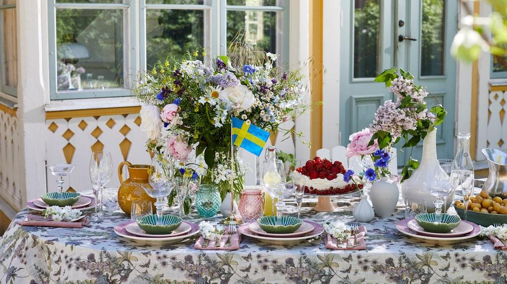 Flaggstång, 699 kronor, Cervera. Stor glasvas, 395 kronor, Floristkompaniet. Ljuslyktor i glas, 50 kronor styck, H&M home. Duk med blommor, 240 x 170 centimeter, 299 kronor, Hemtex. Gul karaff, 449 kronor, Potteryjo.