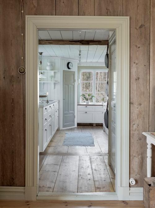 Köket har fått ett rymligt platsbyggt skafferi. Väggens brädor i förgrunden har tidigare varit innertak i ett rum på husets vind och har nu fått bilda en vacker brädvägg.