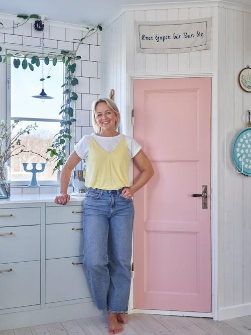 Julia framför skafferiet som är platsbyggt. Dörren kommer från ett gammalt hus som skulle rivas. Bonad, lampa, vas och ljusstake från loppis.