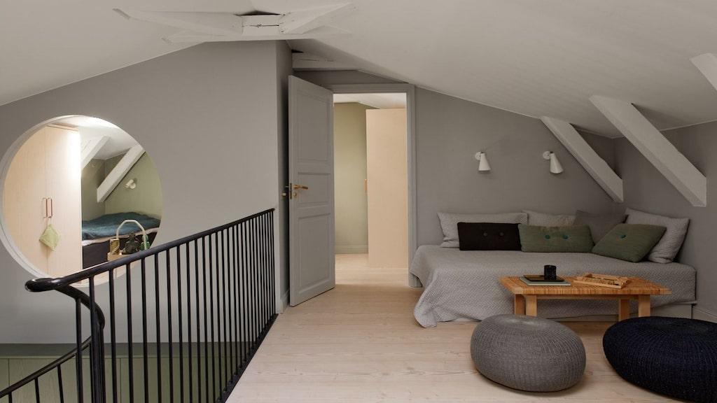 Ovanför trappan hamnar vi i detta mysiga allrum med loungekänsla på andra plan. Räcke och öppen sikt ned till första våningen.