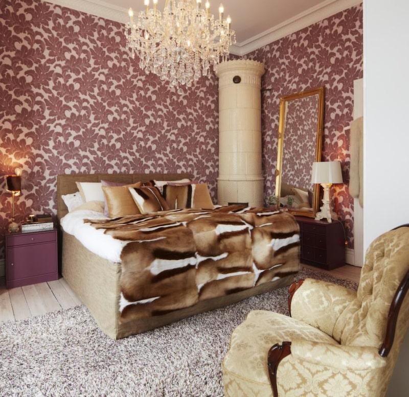 I sovrummet blandas beige färger med toner av aubergine och gulddetaljer. Medaljongtapet, Designers guild.