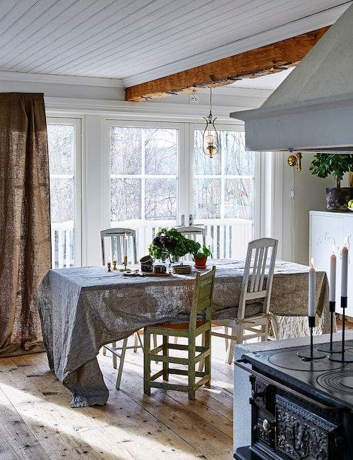 Den gamla gjutjärnsspisen ger köket karaktär. Rummet badar i ljus från de stora glasdörrarna som leder ut till altanen. Stolarna är loppisfynd. Bordduk från Linum. Gardiner, Himla.