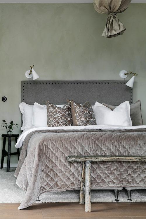 Väggen i sovrummet är målad med kalkfärg. Sänggaveln har Anders gjort. Lampor, kuddar och överkast, Day Home. Pall och träbänk, Snowdrops Copenhagen, Taklampa, PR Home.