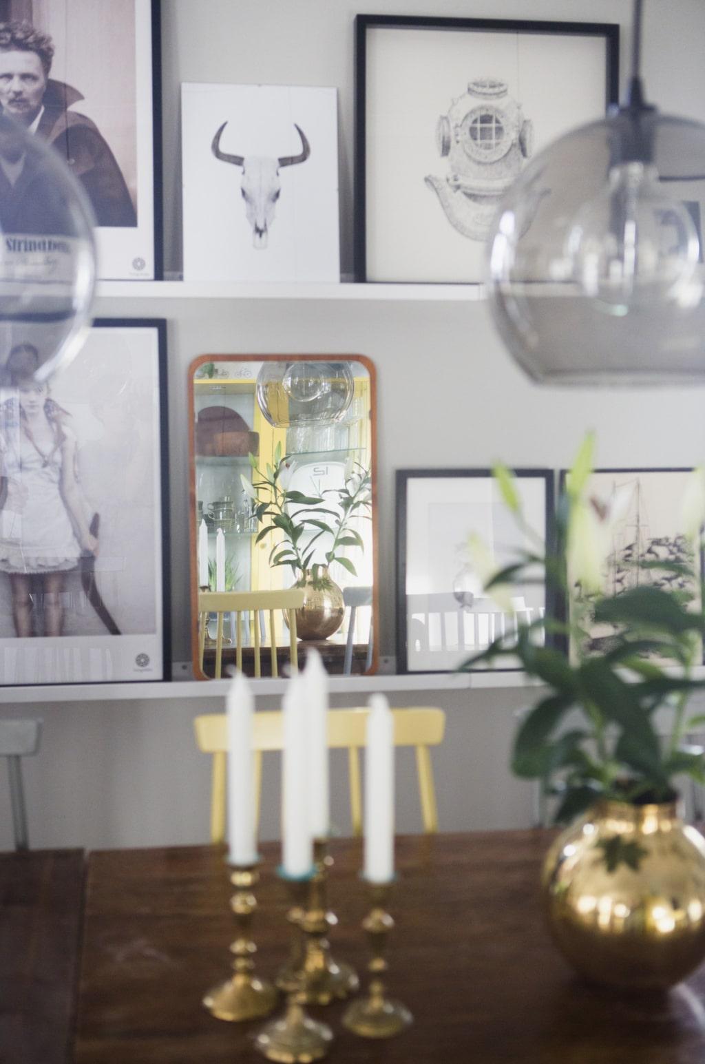Mässing. På bordet står en vas från Skultuna messingsbruk och några gamla mässingsljusstakar. I bakgrunden syns parets tavelsamling.