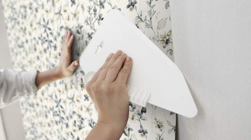 Använd borste, svamp eller spackelskrapan för att släta ut tapeten och få bort överflödigt klister och luft under den.