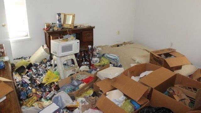 Golvet täcks av lådor fulla med sopor tillsammans med ölburkar och tomma matkartonger.
