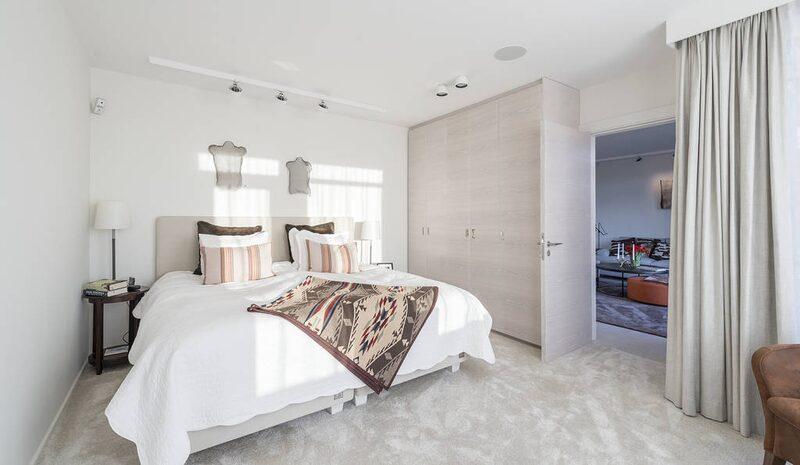 Master bedroom på nedre plan med dubbeldörrar till söderaltanen och eget stort badrum med välutrustad men dold tvättstuga. Platsbyggd garderobsvägg i vitpigmenterad ek och heltäckningsmatta.