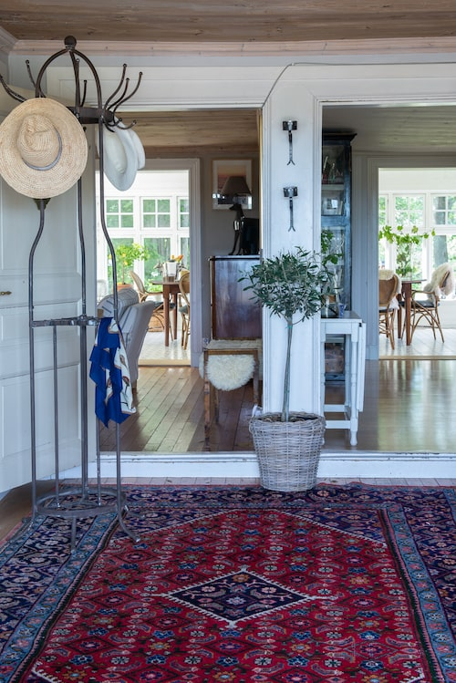 I hallen ligger en stor matta köpt på auktion. Härifrån kommer man in i vardagsrum och kök, men även sovrum.