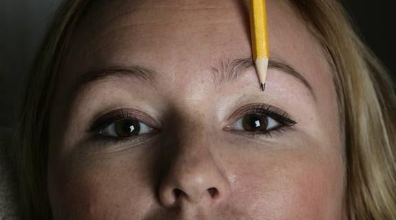 4. Högsta punkten. Måtta sedan med pennan vid mitten av iris. Rakt ovanför iris ska brynets högsta punkt vara.