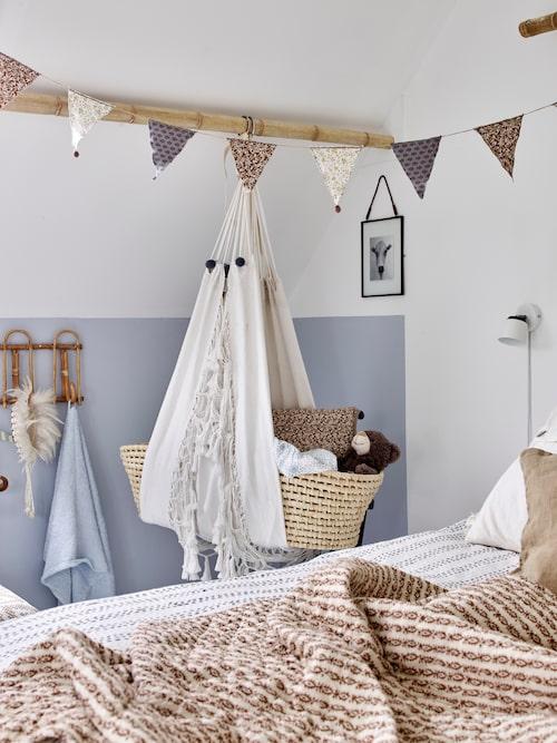 Kirsten har tillverkat en hängvagga genom att kombinera en moseskorg och en hängstol. Girlangen med vimplar har Kirsten har tillverkat.