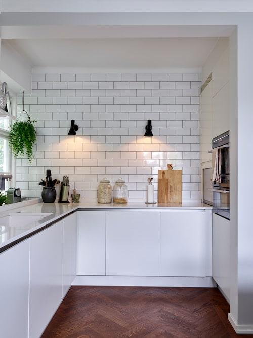 Paret har valt att kakla kökets vägg upp till taket för att ge en industriell och gedigen känsla. Vägglampor AJ, design Arne Jacobsen.