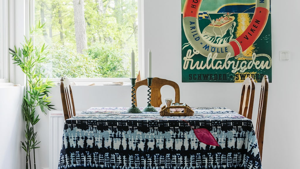 """Det stora bordet ska bytas ut mot ett tunt. """"Just nu är det för mycket fyrkantiga former i köket, det behöver mjukas upp"""", säger Stina. Duken är ett draperi från Indiska. Affischen symboliserar Stinas uppväxt på Kullahalvön och är köpt i Sjöbutiken i Höganäs."""
