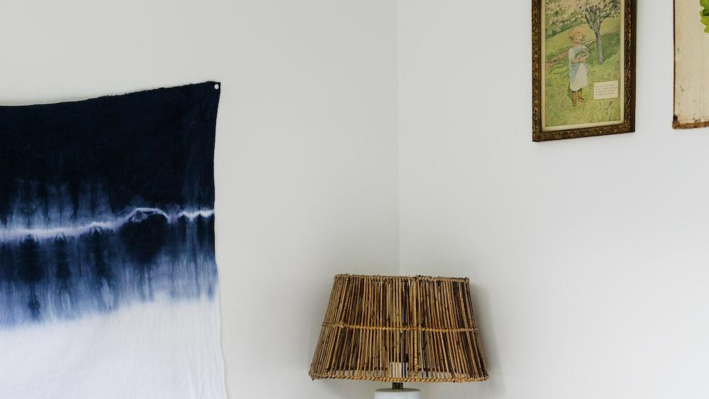 """Teds och Stinas sovrum är litet men funktionellt. På väggen hänger ett vitt linnetyg färgat i blå nyanser av Stina, och fäst på väggen med häftstift. """"Världens enklaste sänggavel"""", tipsar Stina. Lampfot från loppis med skärm från Tine K home."""