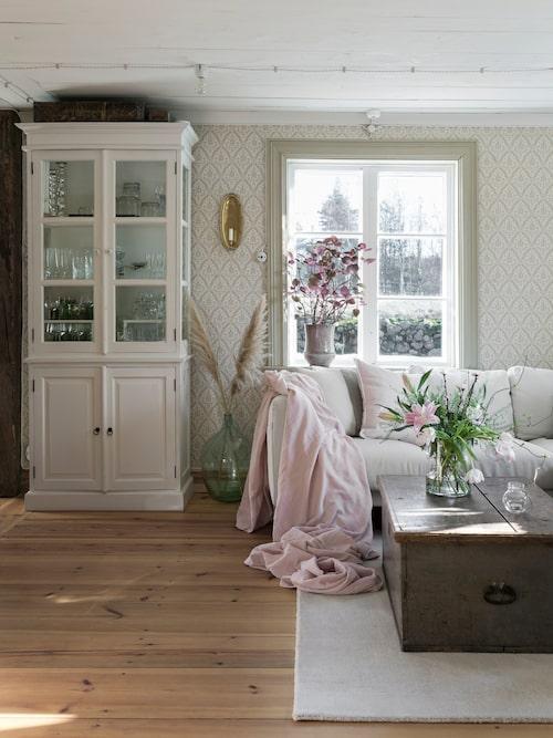 Vardagsrummet är inrett i ljusa toner där den vackra gammaldags tapeten ger rummet en fin känsla. Tapet, Rydeholm Kvist/Rosa 1870, från Lim & Handtryck. Skåpet hittade Jessica på loppis. Soffa från Ikea.