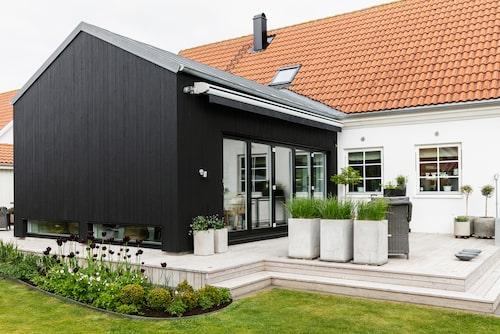 """Efter en utbyggnad av matrummet blev det två terrasser. Den sydliga används för att fånga eftermiddagssolen. I de tre grå krukorna växer tuvrör """"Karl Foerster""""."""