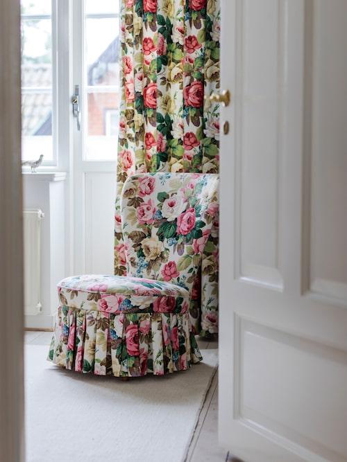 Dottern Ellens rum är inrett med blommiga tyger, här är det samma mönster på gardinen och på Emmastolen. Elisabet anlitar gärna en tapetserare för att klä om auktionsfynd med tyger hon valt ut.