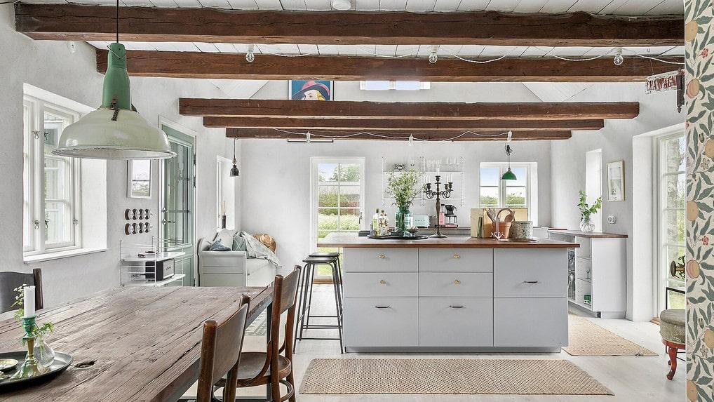 Vackra takbjälkar i det rymliga köket med stor köksö och matplats-del.