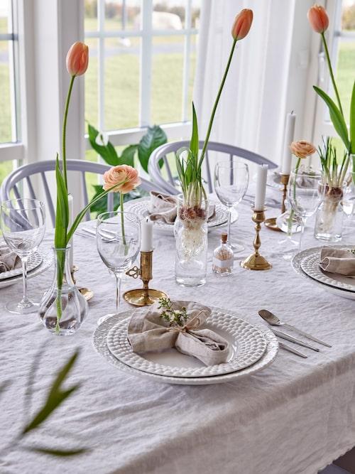 """""""Jag tycker mycket om att göra vackra dukningar och använder mig gärna av flera mindre vaser för att skapa ett snyggt blickfång"""", säger Sarah. Tallrikar, Mateus, krokusvas, Granit, linneservetter, Ikea, blommor, Magasin L i Habo. Ljusstakarna är loppisfynd."""