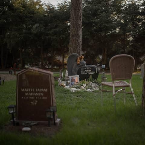 En ensam stol står framför Marley Åsard Fredrikssons grav. En ljusbrun teddybjörn vilar på stenen.