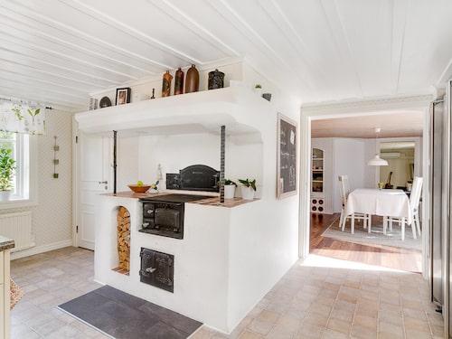I köket finns en fin gammal vedspis med kåpa och mycket praktiskt skafferi bredvid.