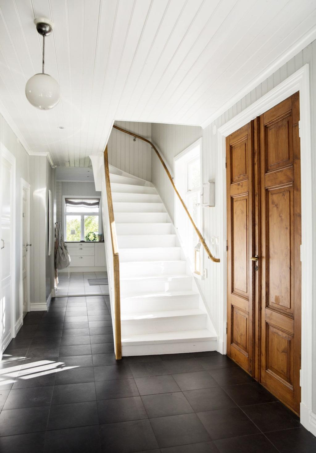 Hallen är klädd med svarta plattor, och trappen är målad vit. Dörrarna och trappräcket är i originalskick.