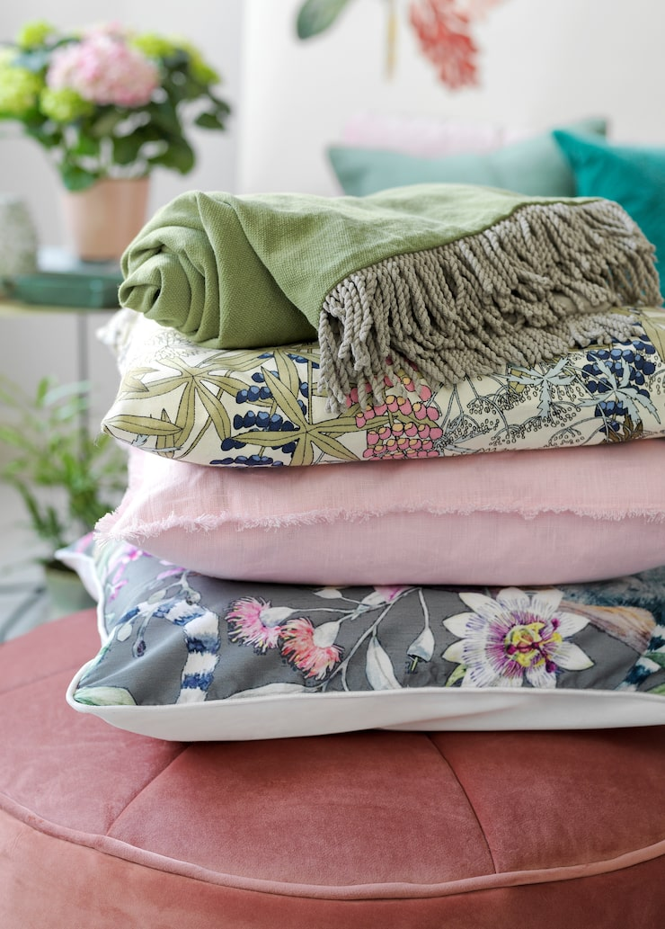 Grå blommig kudde, 395 kronor, Classic collection. Rosa kudde, 399 kronor, blommig kudde från Linum, 299 kronor, Nk inredning. Grönt tyg med frans, 1 495 kronor, Top Drawer.