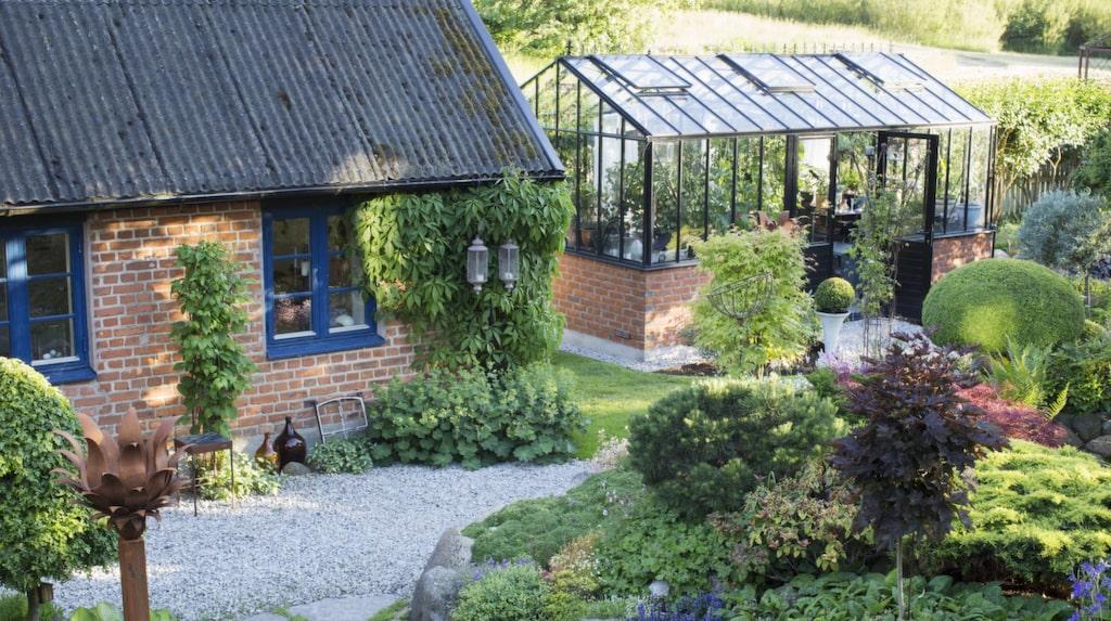 Utsikt över Pers smedja och det vackra växthuset. Tegelmuren på växthuset går igen i smedjan. Vildvinet på smedjans vägg får en fantastisk färg på hösten.