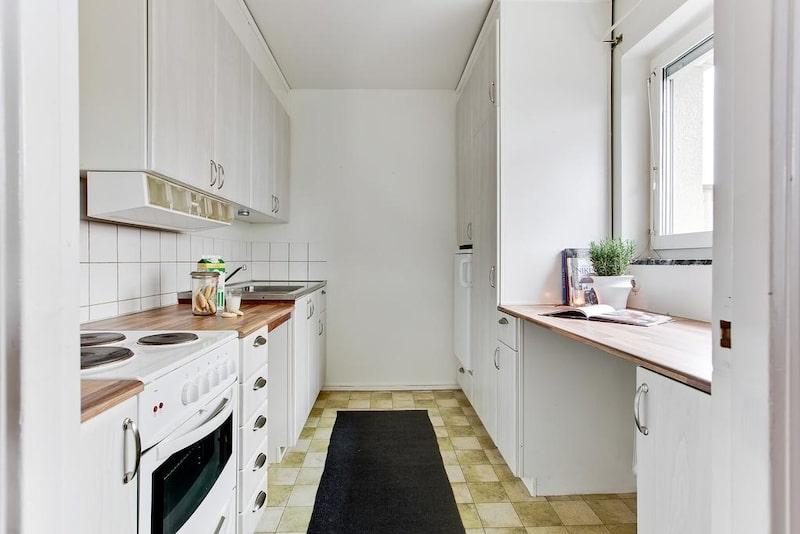 Bostaden har ett ljust kök med plats för allt det nödvändiga. Ljusinsläpp från Ljusare luckor i vitlaserad ekfärg och köksbänken bryter av i mörkare nyans.