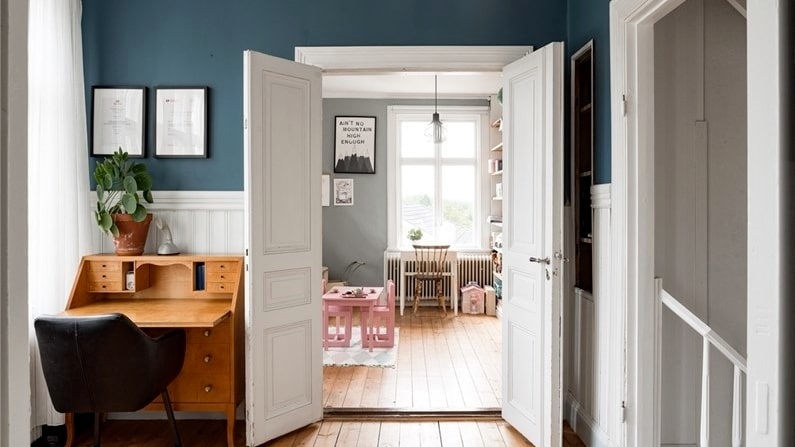 Hall på övervåningen med original trägolv och pampiga pardörrar in till ett av sovrummen.