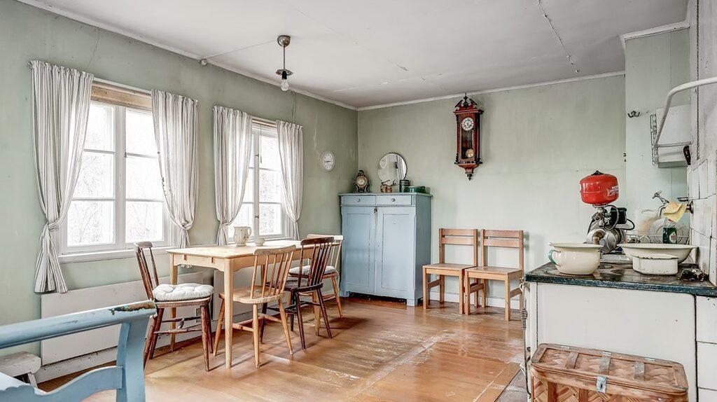 Ett rejält kök med matplats. Trägolv och målade väggar samt vedspis.
