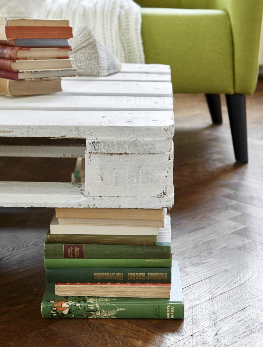 Här är ett charmigt alternativ till bordsben. Lastpallen lades på fyra stycken boktravar och blev tillsammans ett personligt soffbord. Köp gamla böcker på loppis, skolbasarer eller auktioner. Lägg ut böckerna i fyra jämna travar och limma ihop pärmarna med varandra. Lastpallen är så pass tung att den ligger stadigt utan att fästas.