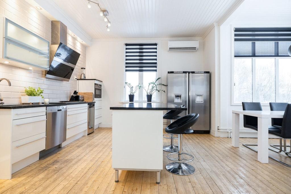 Det stora köket renoverades 2008 med ett vitt Mobalpakök som kompletterats med svarta granitskivor och en köksö. Här finns en rejäl spishäll från Husqvarna som rymmer både spisplattor, fritös och grill. Övrig utrustning är vinkyl och stor fläkt från Franke, inbyggd ugn som även är en mikrovågsugn från Siemens, diskmaskin, kyl och frys med kallt vatten (både med och utan kolsyra) samt ismaskin från Electrolux och en fungerande kakelugn. Via köksingången kommer man ut till den nybyggda trivsamma altanen.