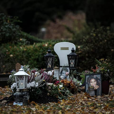 Karolin Hakims grav är täckt av blommor, ljus och foton. Runt graven ligger höstens bruna löv, våta av regnet.