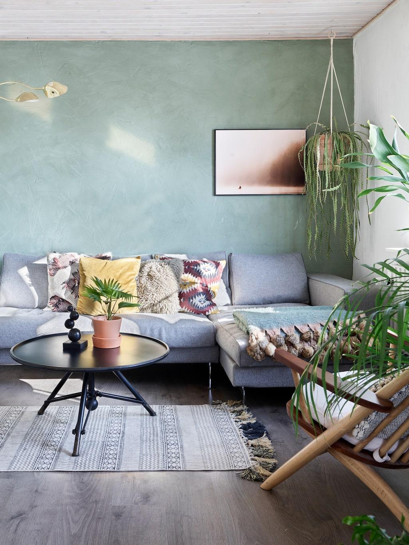 I vardagsrummet har paret målat en grön fondvägg med spackelfärg från Fil, i nyansen Antique green.