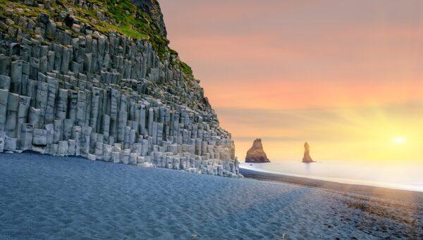 Vid kanten av Reynisfjara reser sig dramatiska klippformationer som kallas Reynisdrangar.