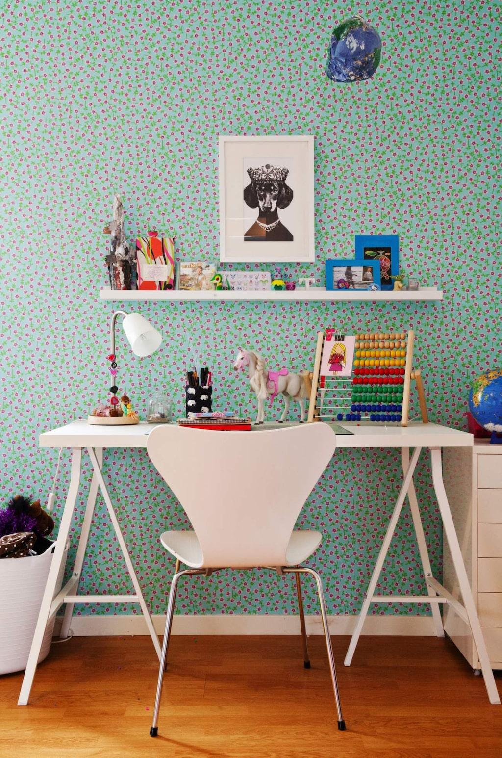 """<p>Glada prickar. Tapeten från Designers Guild, """"Prim Rose"""". Bockar, skiva och hurts från Ikea. Stolen är en gammal Sjuan. På väggen sitter bland annat en illustration från Lisa Bengtsson, taxen """"Ulrika Eleonora"""".</p>"""