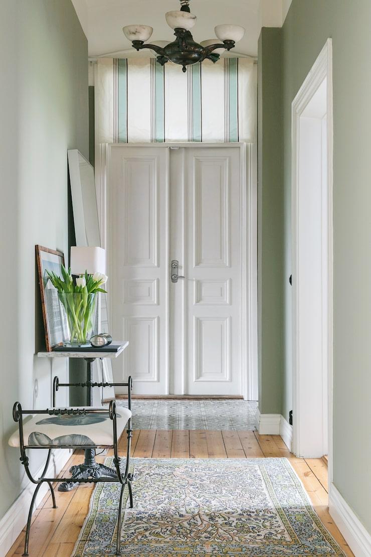 I den ljusa hallen, målad i en lindblomsgrön färg står ett litet möblemang som Suzana har ritat själv och låtit tillverka. Väggen är målad med en kulör från Farrow & Ball.