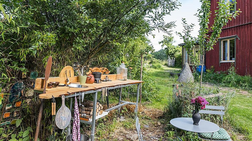 Ett utomhuskök, med arbetsbänk och diskho, är ett måste på en sådan här gård.