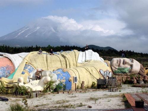 En jättelik staty av Gulliver, fastsurrad till marken med Mount Fuji i bakgrunden.