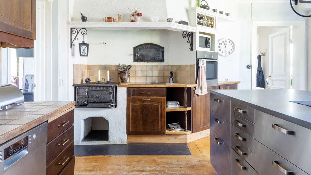 Kök på entréplan med renoverad vedspis med spiskåpa, spishäll, spisfläkt, kyl/frys, diskmaskin och platsbyggt skafferi.