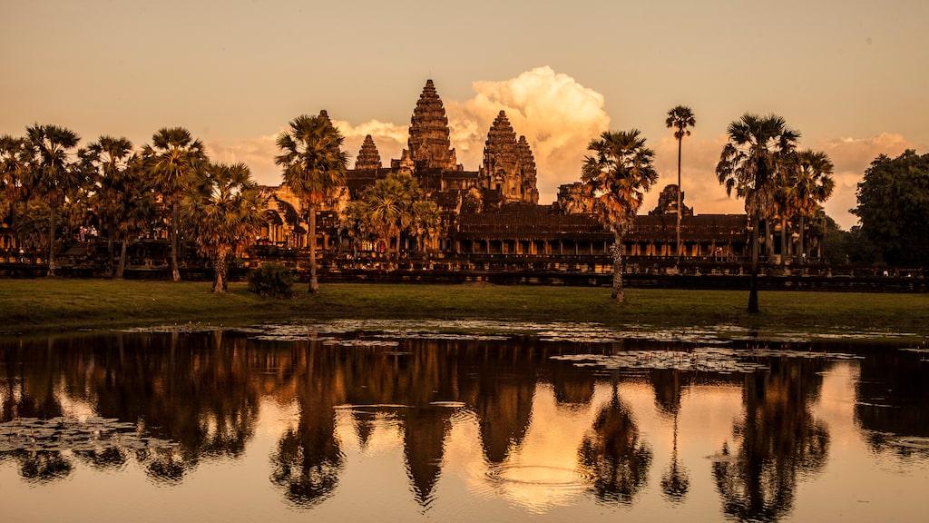 I solnedgången färgas Angkor Vats stenbyggnader i varma toner, medan solen sjunker i väster.