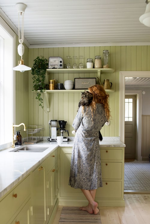 Frida i det nyrenoverade köket. Hyllorna är original som är ommålade.