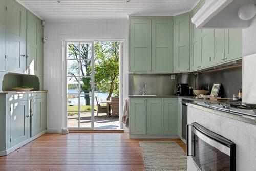 Platsbyggt kök i ljusgrön nyans och stora glasdörrar med utsikt över poolen och sjön.