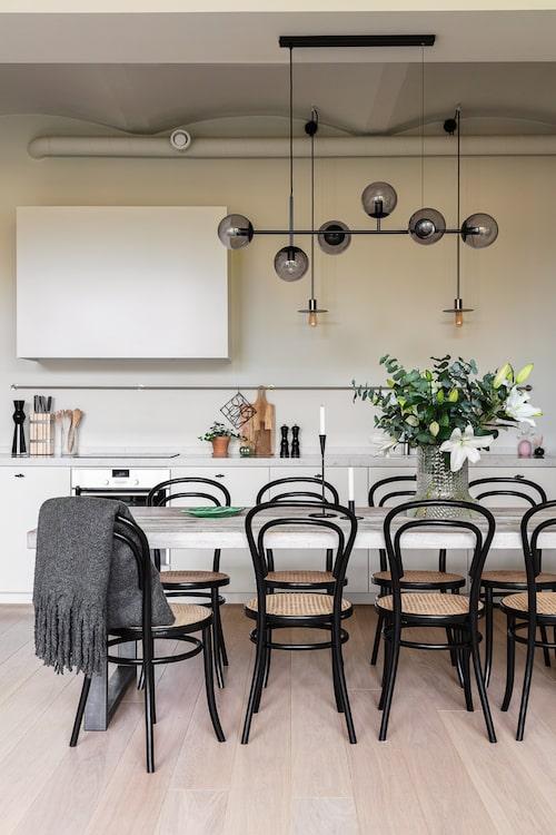 Lägenhetens kök och matplats har plats för stora middagar med många gäster. Industrikänslan är bevarad i köket som saknar överskåp. Det ger en luftig känsla och får den generösa takhöjden att upplevas som ännu högre. Köksbord, Mio. Köksstolar, Ton. Taklampa, Bolia. Glasvas, Skruf Sweden.