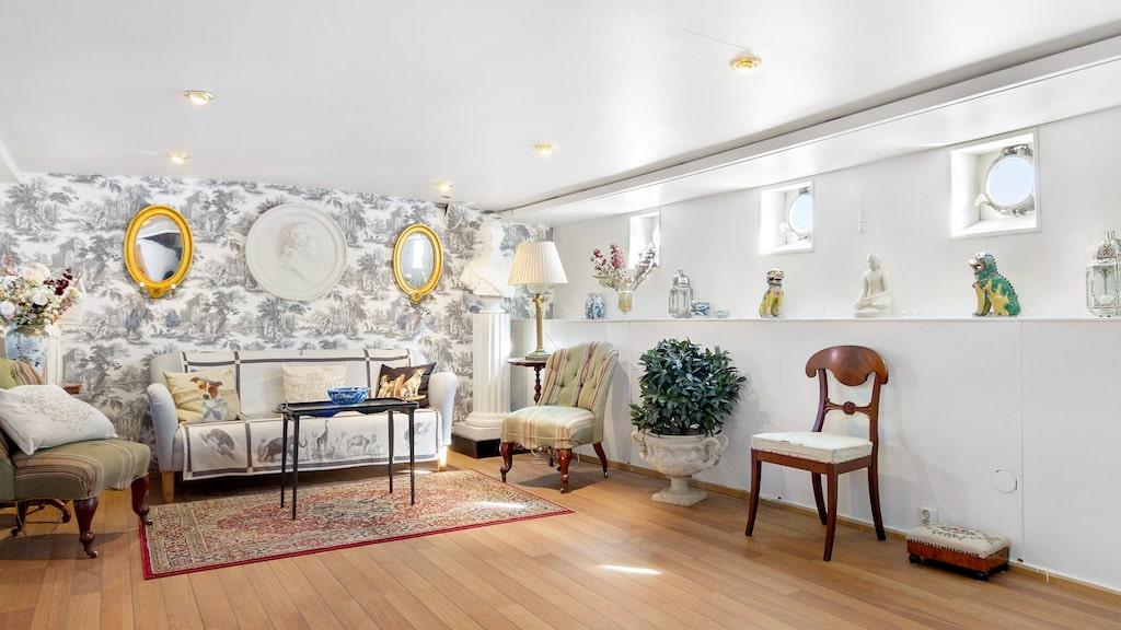 Vardagsrummet är målat i vitt med snygg dekorativ fondtapet och trägolv.