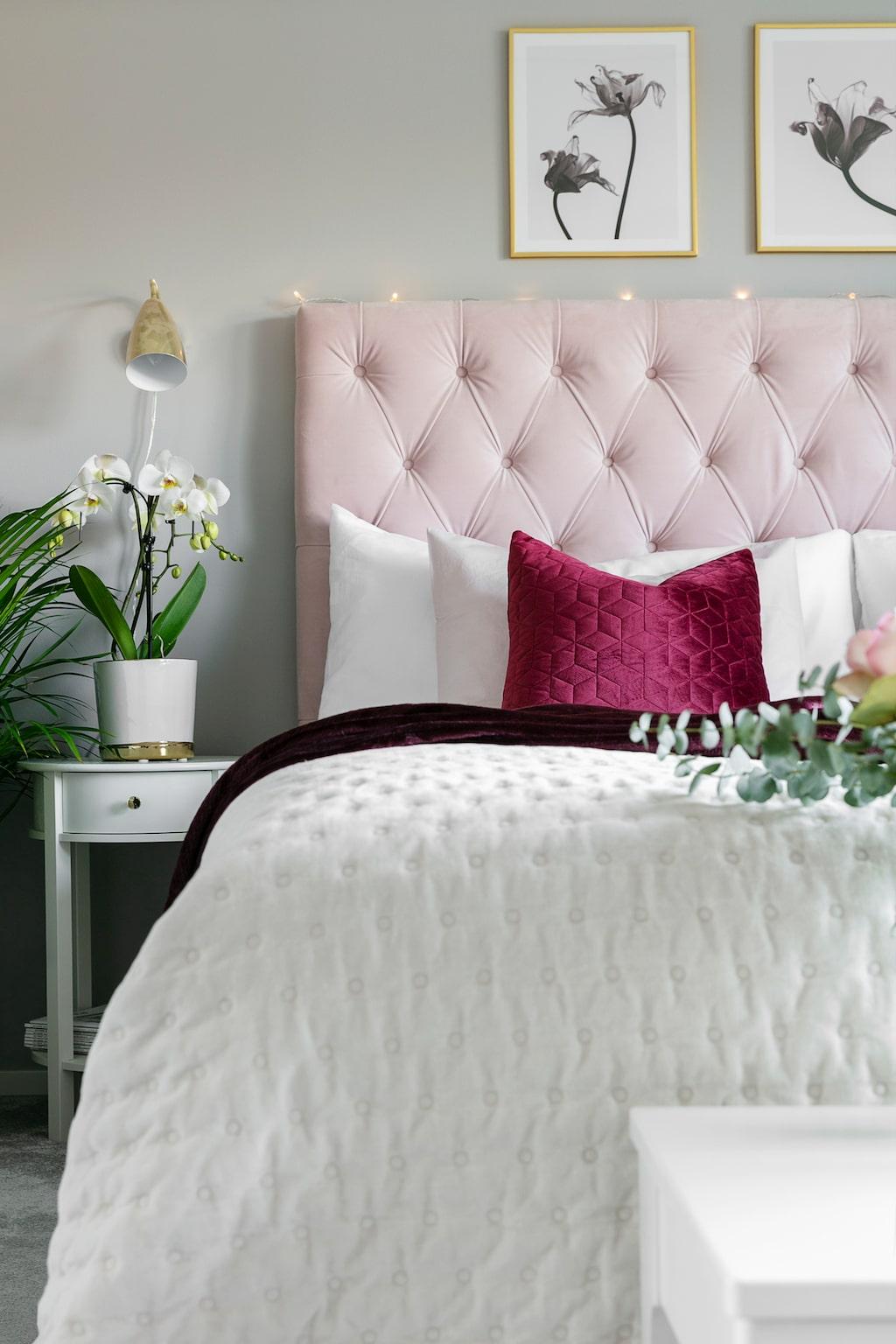 """Sängen i det ombonade sovrummet, som för tankarna till ett lyxigt hotellrum, är alltid bäddad med kuddar och överkast. Sabina mår bäst av att ha det rent, snyggt och städat. """"Jag går och plockar hela tiden"""", förklarar hon. Nattygsbord Jysk. Säng, Ikea, med sänggavel från Ellos. Överkast, Jotex. Kuddar Rusta. Sänglampa, Jotex."""