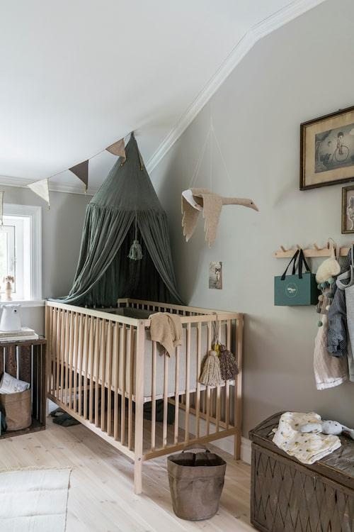 Nils rum är mysigt och ombonat. Väggarna är målade i kulören House of Philia Greige från Nordsjö, sänghimlen kommer från Kongesslöjd, sängen från Ikea, svanen från Wonderforest co och vimpeln från Numero 74.